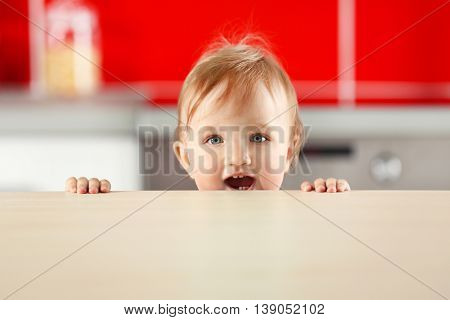 Child looking over kitchen counter