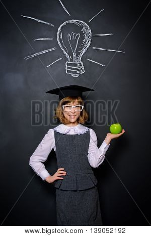 Educational concept. Smiling schoolgirl standing with green apple by a blackboard. New idea. Copy space.
