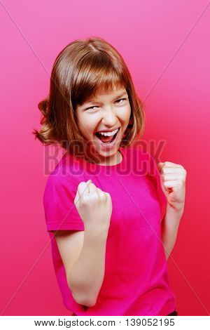 Portrait of a joyful smiling teen girl over pink background. Gladness and success.