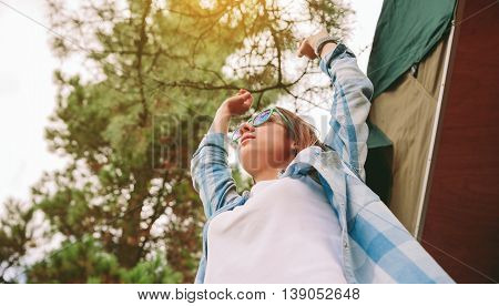 Below view of young beautiful woman with sunglasses and blue plaid shirt raising her arms over a sky and trees background. Freedom and enjoy concept.