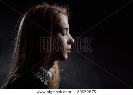 sad blond girl crying on black background