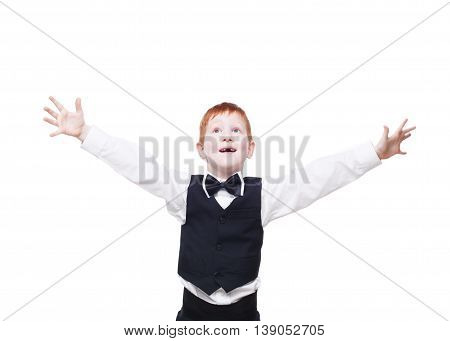 Little cute excited and happy redhead boy in vest with bow tie pose with raised hands. Portrait of well-dressed emotional child, looking up delighted isolated on white background