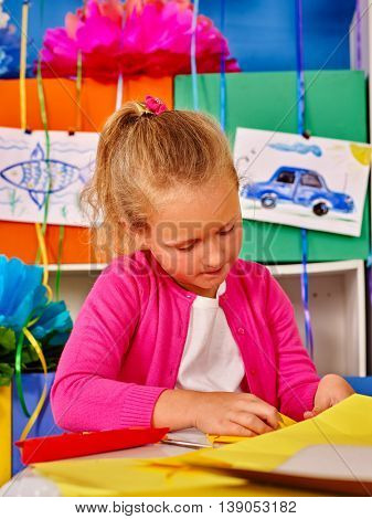 Portrait of school child girl make of colored paper on table in primary school.