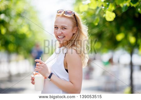 Pretty smiling woman with milkshake on nature background