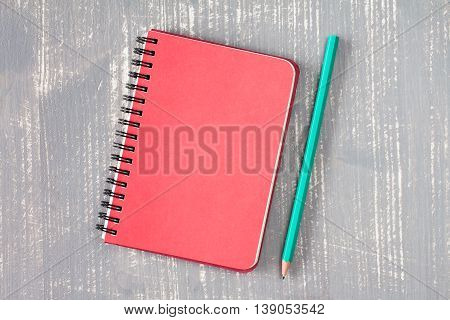 Spiral notebook and pencil over grey wooden background.Copy-space.