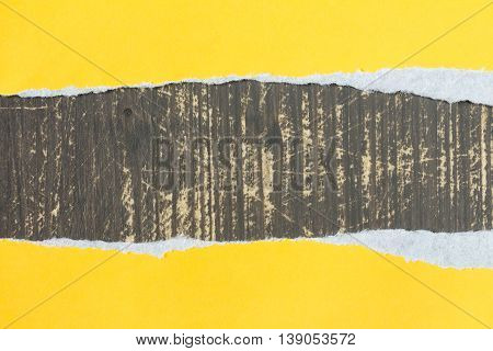 Torn yellow paper with a wooden background for your text.
