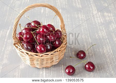 Wicker basket full of fresh cherry fruit on the grey wooden surface