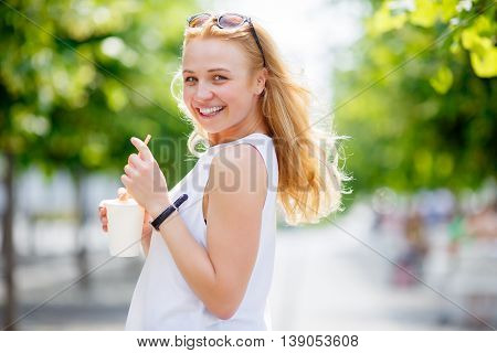 Outdoors portrait of cute blonde with milkshake showing tongue