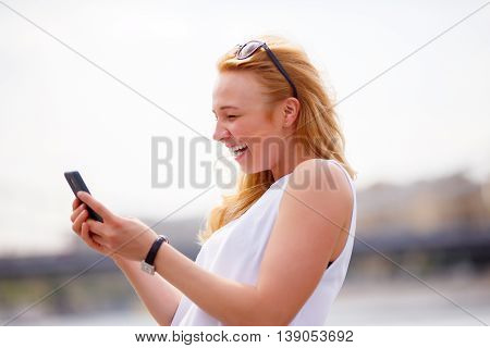 Woman receiving good news on her mobile phone. Human emotion, expression and reaction