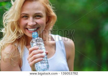 Closeup portrait blonde girl holding plastic bottle of water