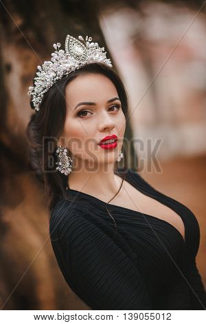 Beautiful woman model with professional makeup, in jewelry. Golden crown