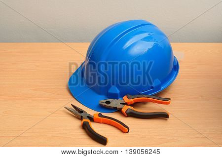 A blue hard hat displayed with a set of pliers and a long nose pliers