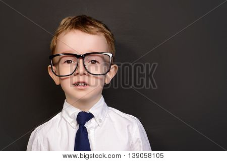 Four year old boy in white shirt and a tie posing by a school blackboard in big glasses. Educational concept.