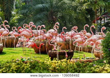 Flock of pink flamingos. Garden scultures in the Nong Nooch garden. Decorative statues of large exotic birds. Pattaya Thailand.