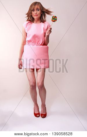 Young woman in pink mini dress frightened as a gust of wind under your skirt blows - Studio shot isolated on gray