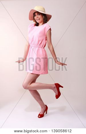 Full length studio portrait of a stylish young woman posing against a gray background