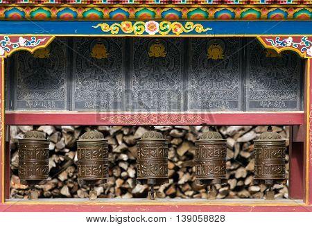 Buddhist prayer mani wall with prayer wheels in nepalese village on the Annapurna circuit trekking route, Nepal