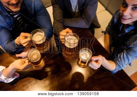 Midsection of friends toasting beer at restaurant