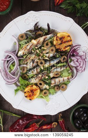 Grilled sardine fish with lettuce, olives and onion