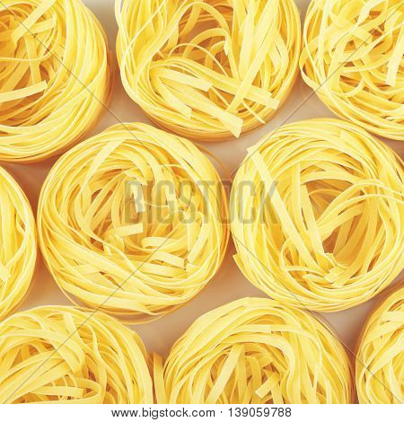 raw pasta tagliatelle nest on table, top view background