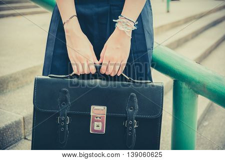Body and hands of cute Asian Thai high schoolgirls student in school uniform holding black leather bag in education fashion in retro vintage childhood concept