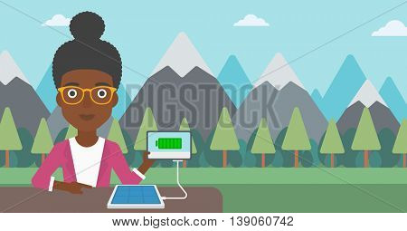 An african-american woman charging tablet computer with solar panel on a background of mountains. Charging digital tablet from portable solar panel. Vector flat design illustration. Horizontal layout.