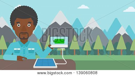 An african-american man charging tablet computer with solar panel on the background of mountains. Charging digital tablet from portable solar panel. Vector flat design illustration. Horizontal layout.