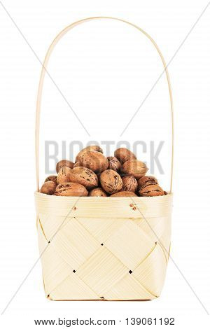 pecan nuts in wooden basket, isolated on white background