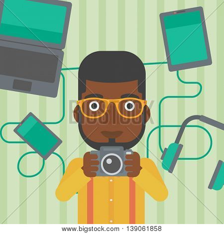An african-american man taking photo with digital camera. Man surrounded with gadgets. Man using many electronic gadgets. Vector flat design illustration. Square layout.