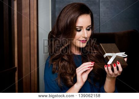 young woman opening a gift box. surprise