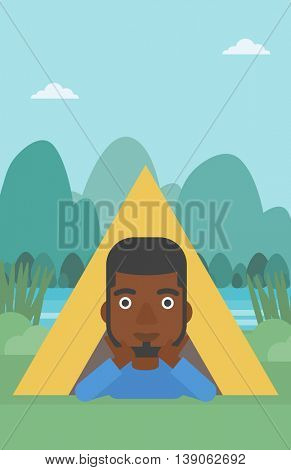 An african-american man crawling out from a camping tent. Man with his hands on cheek lying in camping tent and relaxing. Vector flat design illustration. Vertical layout.