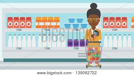 An african-american woman at the supermarket with calculator and supermarket trolley full with products. Woman checking prices with calculator. Vector flat design illustration. Horizontal layout.