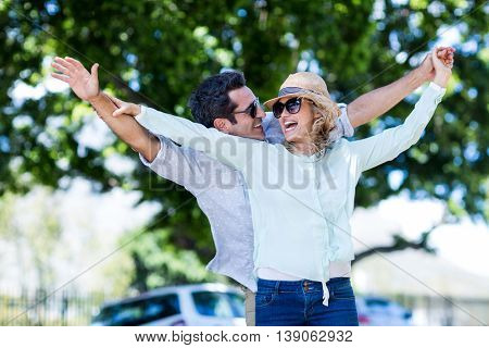 Happy couple with arms outstretched standing against trees in city