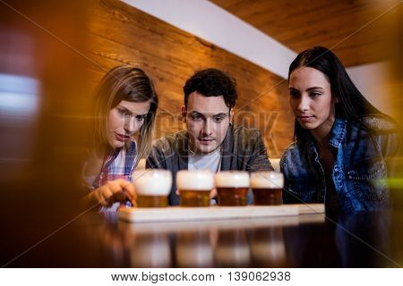 Friends looking at beer glasses on table in restaurant