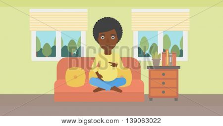 An african-american pregnant woman holding her hands on belly. Young pregnant woman sitting on a sofa at home. Vector flat design illustration. Horizontal layout.
