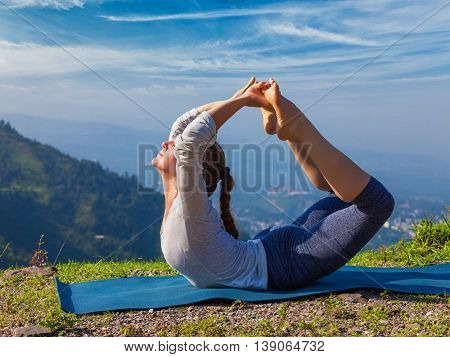 Yoga outdoors - young sporty fit woman doing Ashtanga Vinyasa Yoga asana Dhanurasana - bow pose  - in Himalayas mountains in the morning  Himachal Pradesh, India