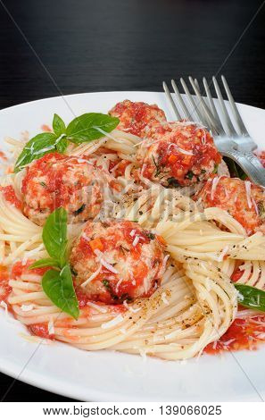 Pasta in tomato gravy with meatballs sprinkled Parmesan and basil