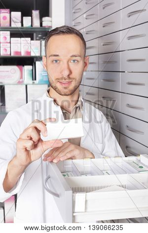 a Young pharmacist at the medicine cabinet