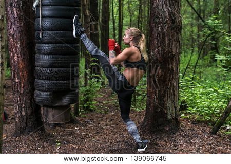 Woman practising kickboxing performing a leg axe kick working out outdoors.