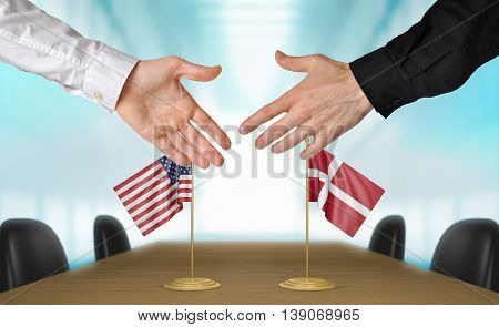 United States and Denmark diplomats shaking hands to agree deal
