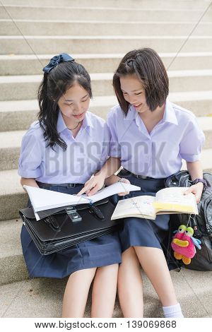Cute Asian Thai high schoolgirls student couple in school uniform sit on the stairway discussing homework or exam with a happy smiling face together