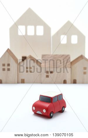 Miniature car and houses on white back ground. Car sharing concept.