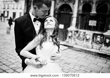Wedding couple near old architecture at wedding day