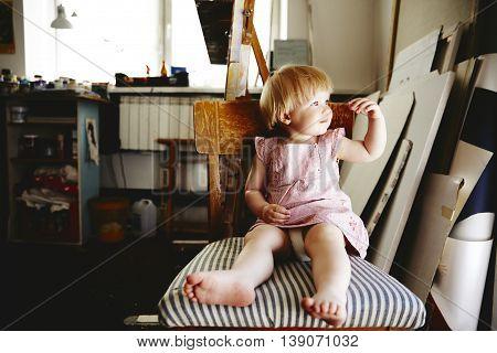 Baby Girl Sitting In Art Workshop