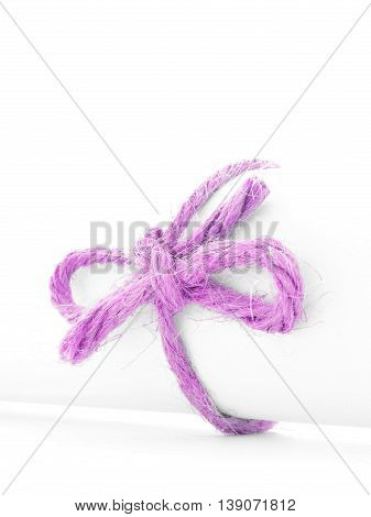 Handmade pink cord bow tied on white paper scroll, isolated