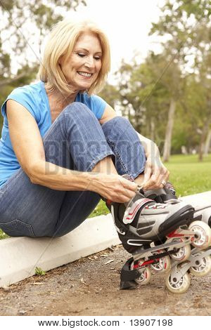 Senior Woman Putting On In Line Skates In Park