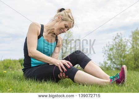 A woman runner hold her sports injured knee