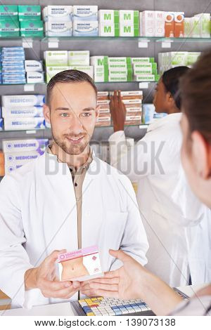 Young pharmacist attending customer and handing over medicine