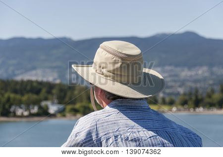 Middle-aged man with a hat looking far at the horizon