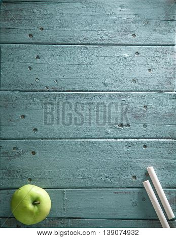 Back to school. School background with supplies. chalk and apple on wood.